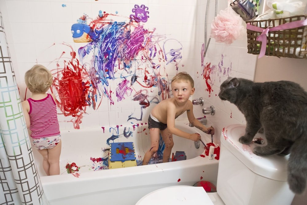 Two kids playing with paint in the bathroom.
