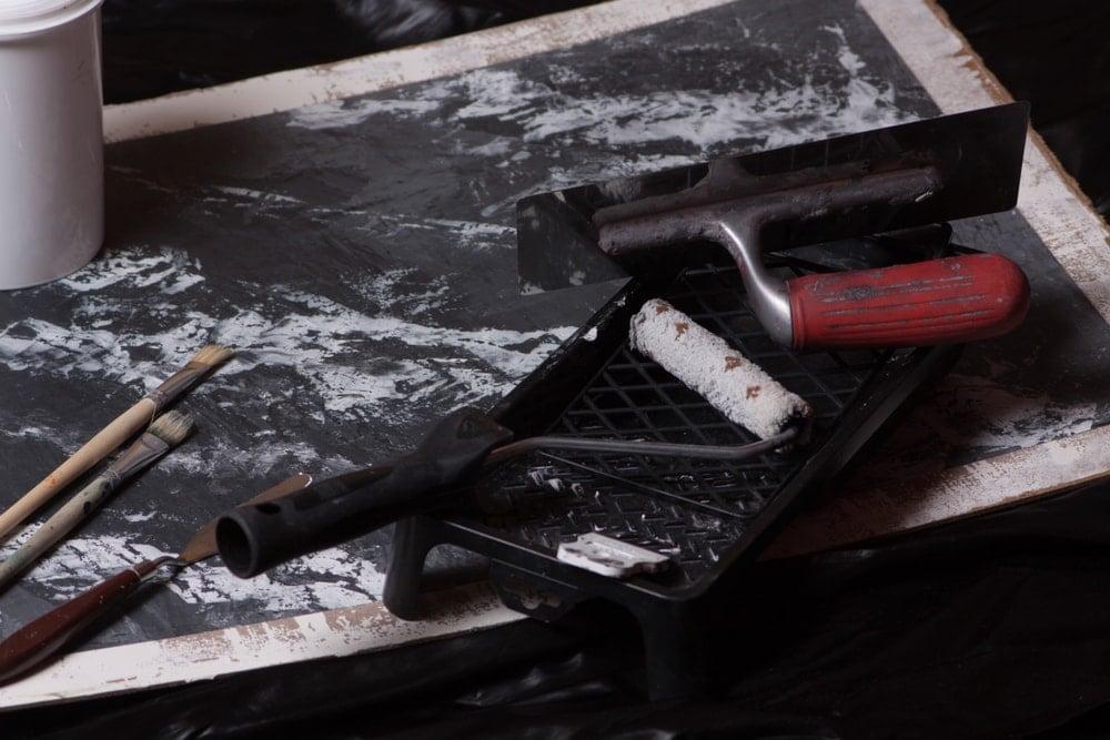 Boya lekeli ahşap bir tahta üzerinde kullanılmış boya malzemelerine yakından bakış.