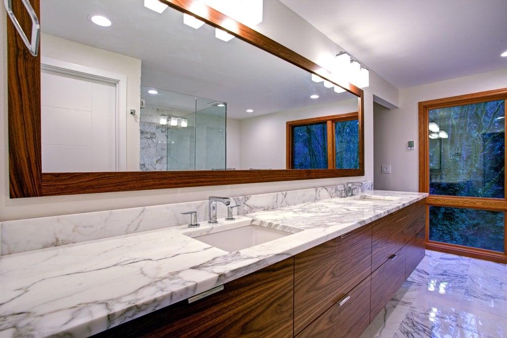 Beyaz granit tezgahlı bir banyonun iki lavabolu makyaj masasına yakından bakış.