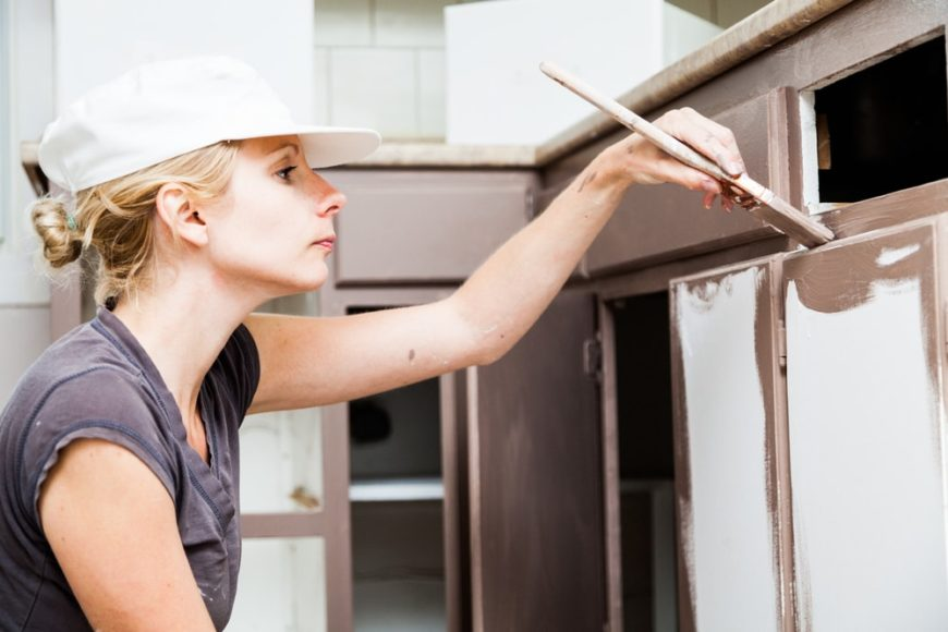 A woman painting the kitchen cabinets with brown paint.