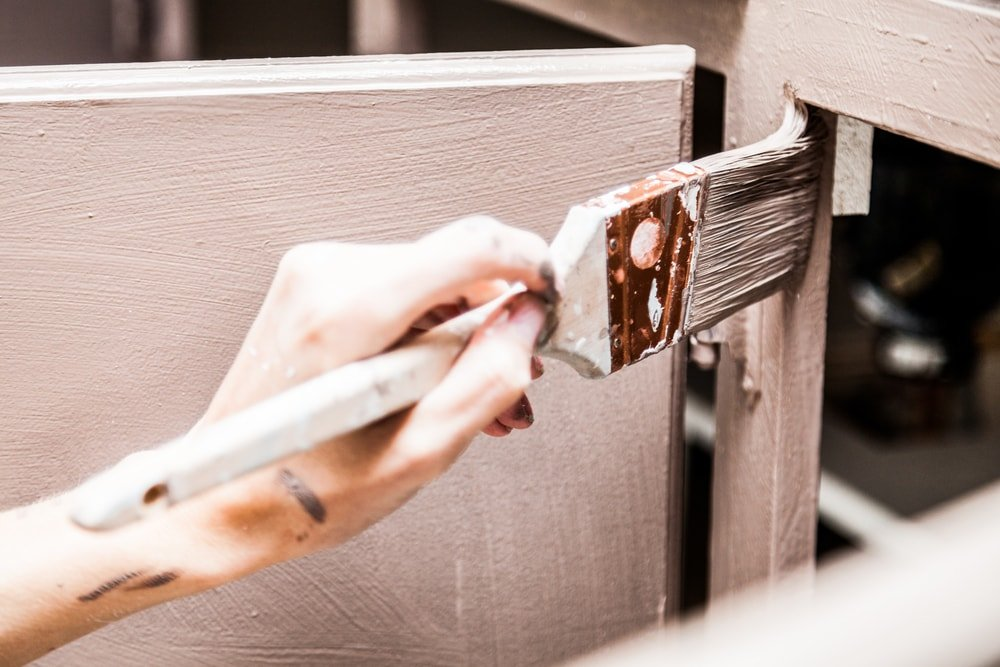 A close look at a kitchen cabinet being painted with the used of a brush.