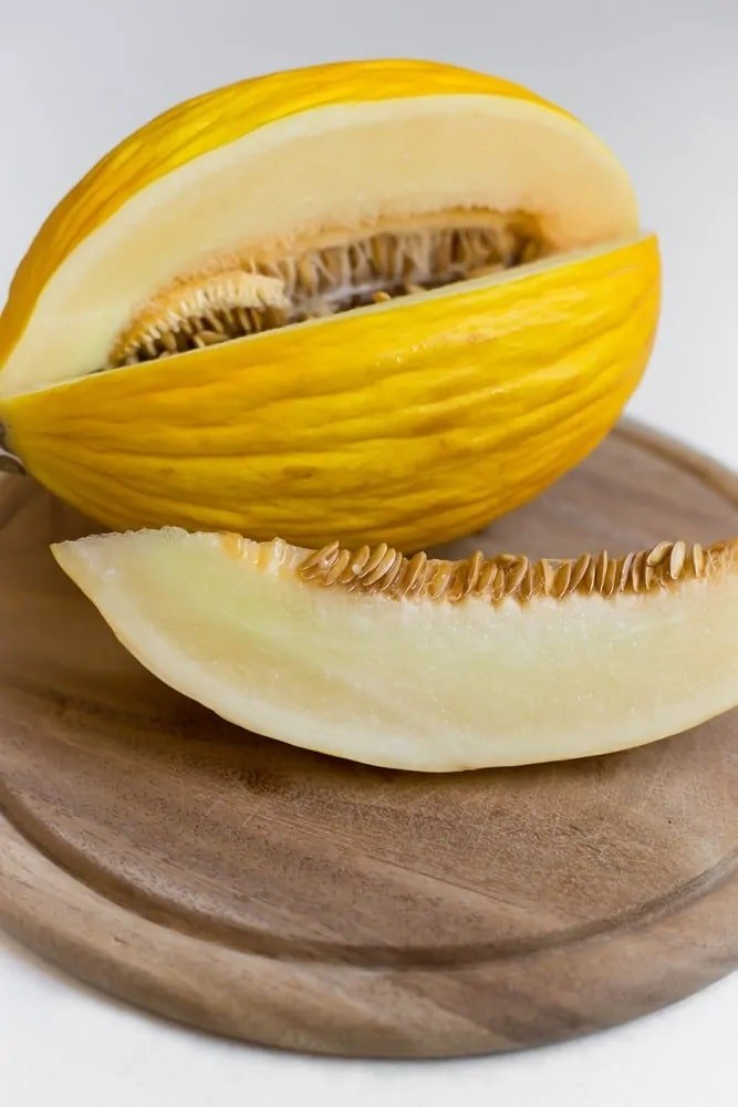 Canary melon on a round chopping board.