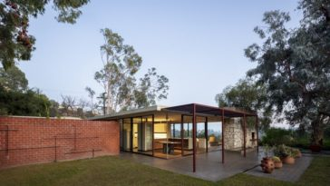 This is a look at the back of the house with a covered patio, a flat roof, lots of glass walls and a large red brick wall. Image courtesy of Toptenrealestatedeals.com.
