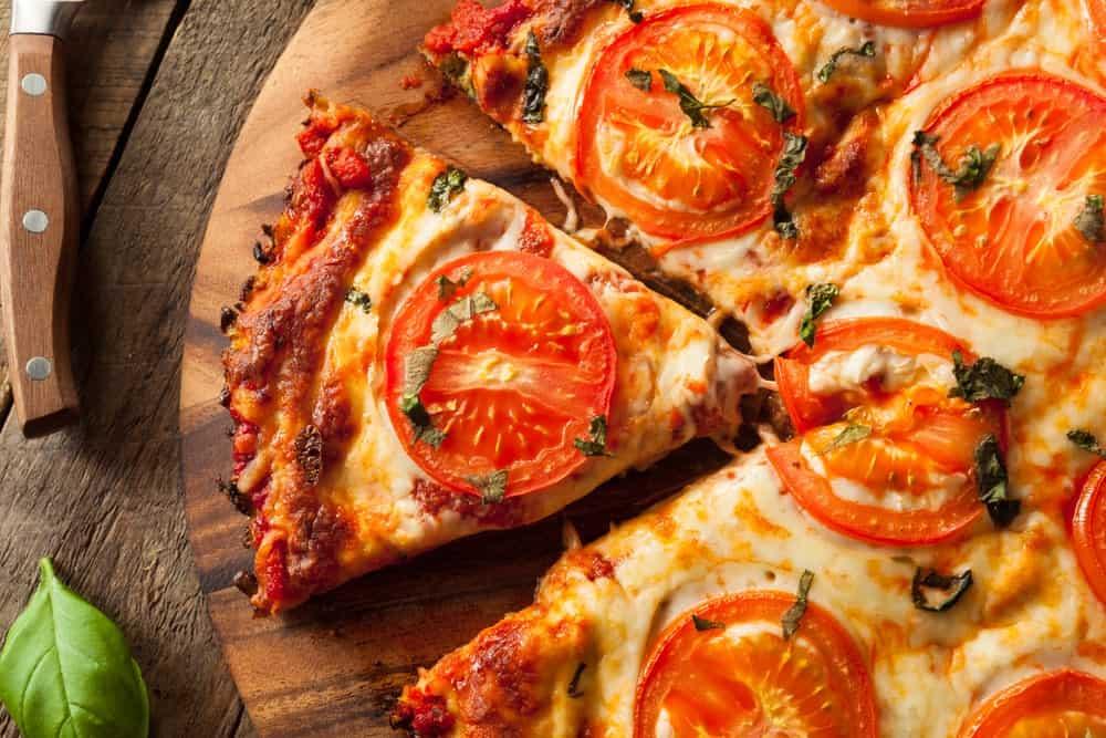 Cauliflower crust pizza on wooden background.