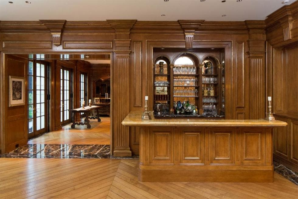 This is the wet bar at the corner. It has a wooden L-shaped peninsula with a wooden countertop and a built-in shelf for alcohol storage. Image courtesy of Toptenrealestatedeals.com.