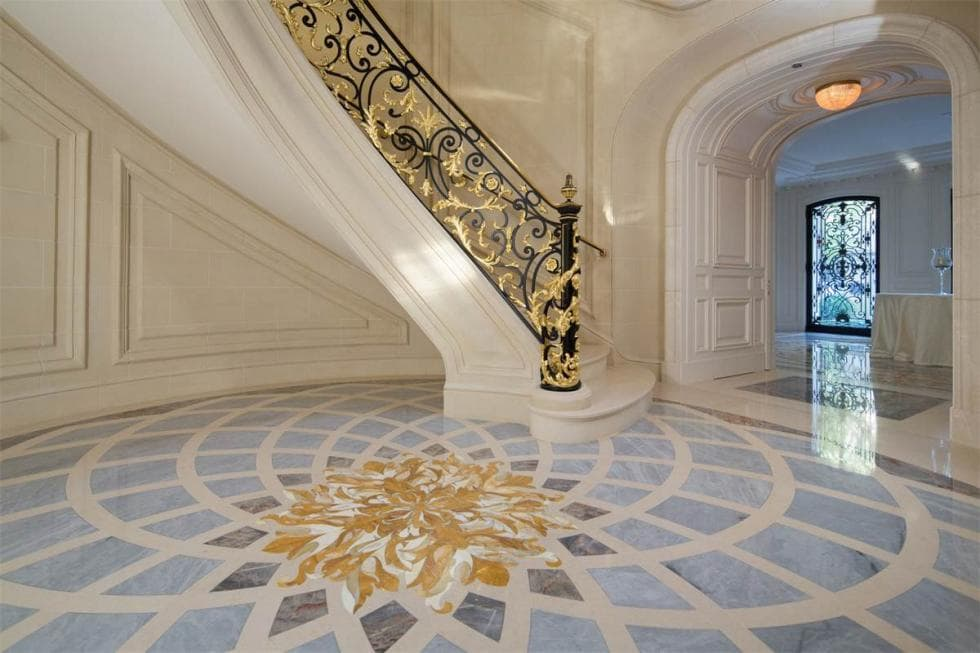 Upon entry, you are welcomed by this grand foyer with a patterned flooring and a beige curved staircase adorned with wrought-iron railings. Image courtesy of Toptenrealestatedeals.com.