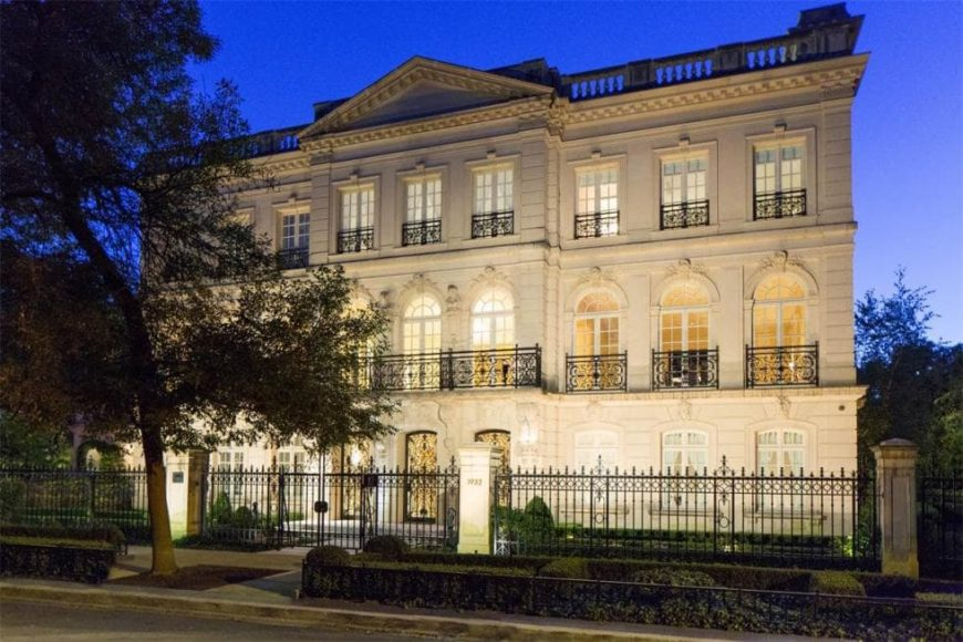 This is a front look at the mansion with three levels, multiple windows and wrought-iron fencing, all complemented by the lighting. Image courtesy of Toptenrealestatedeals.com.