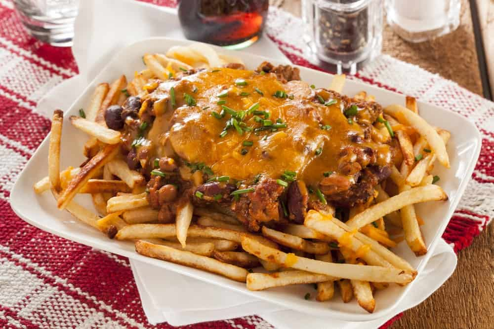 Chili cheese fries served on a white plate.