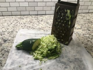 The zucchini is grated on a wax paper.
