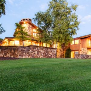 This is a look at the front of the main house adorned with mosaic rock walls and warm lighting that pairs well with the landscaping. Image courtesy of Toptenrealestatedeals.com.
