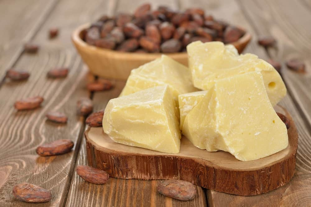 Cocoa butter on a wooden chopping board over a wood plank table.
