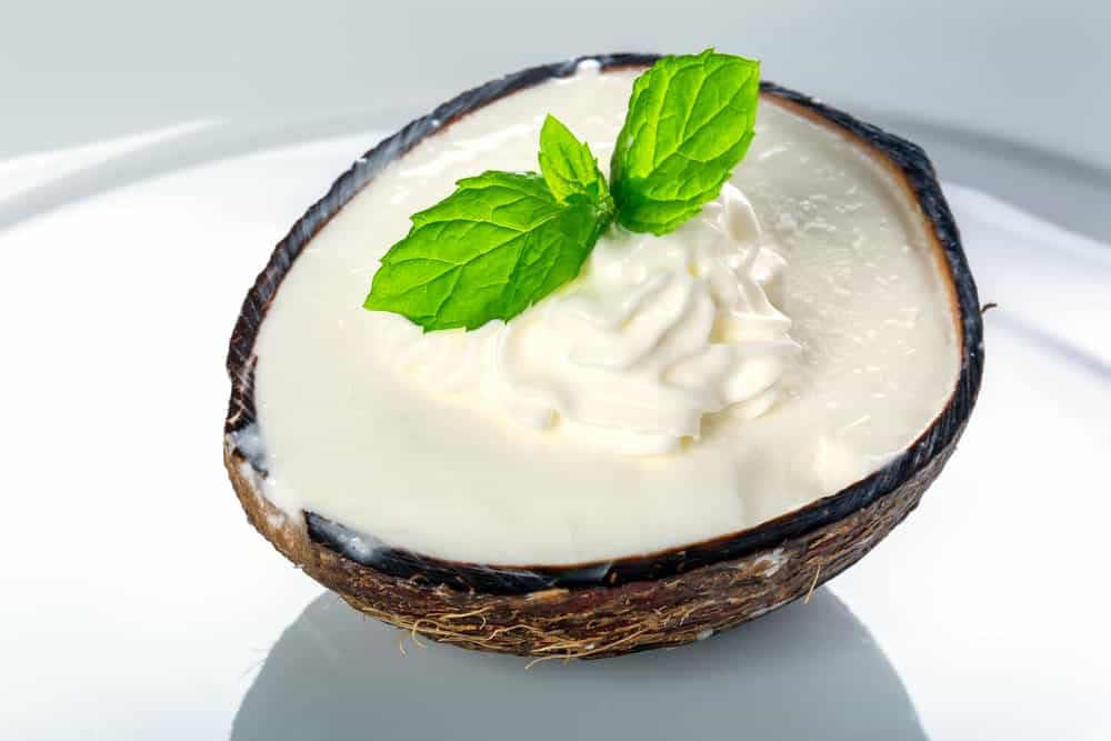Coconut ice cream in a coconut shell with leaves on top.