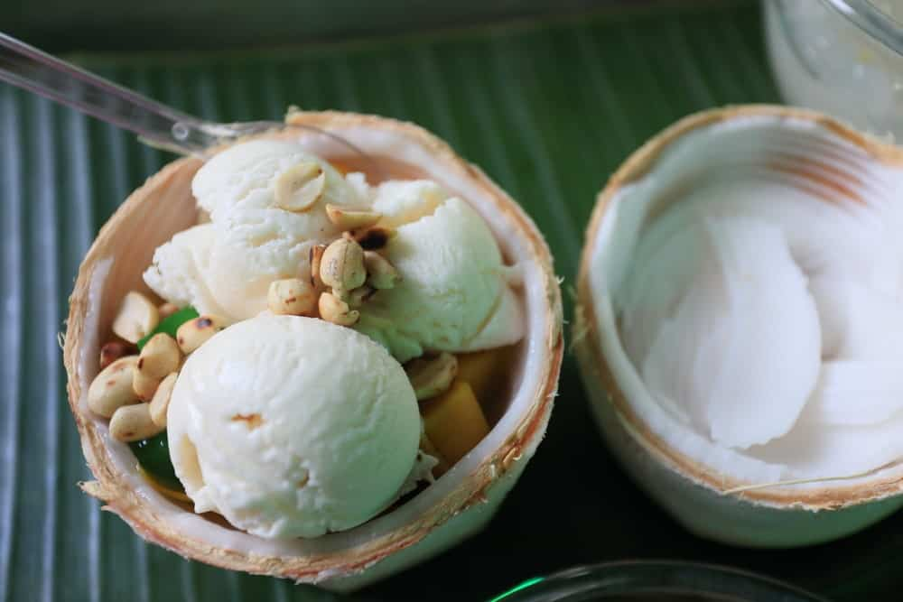 Coconut ice milk in coconut shell over banana leaf.