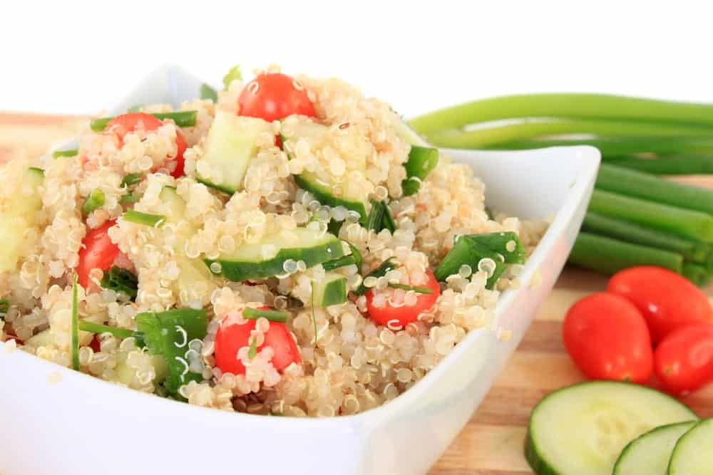 A bowl of cold Quinoa salad with cucumbers, tomatoes, and string beans on the side.