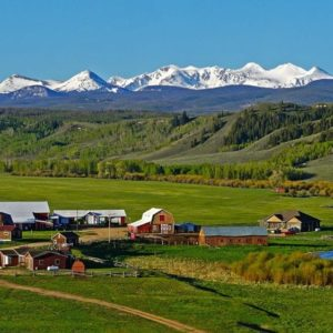 This is an aerial view of the massive ranch with snowcap mountain views, large fields and various structures including the main house. Image courtesy of Toptenrealestatedeals.com.
