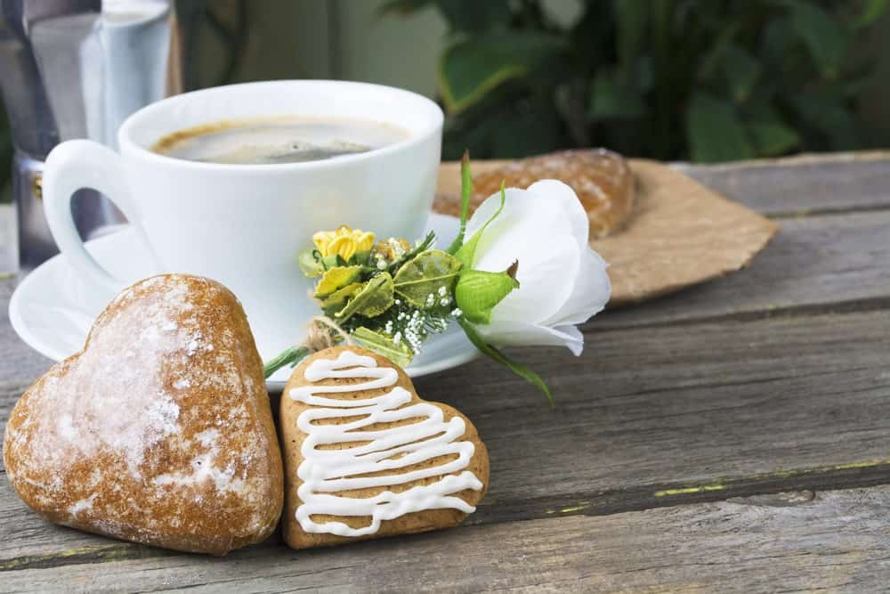 Heart-shaped cookies with a cup of coffee on wooden table.