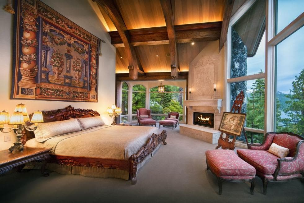 This bedroom has a tall wooden arched ceiling with exposed beams. This is paired with a tall wall adorned by the colorful tapestry hanging over the large dark wood bed. Image courtesy of Toptenrealestatedeals.com.