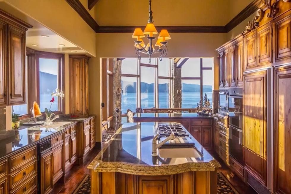 This is the kitchen with dark wood cabinetry that matches the hardwood flooring. The kitchen island has a thick countertop that is topped with a small chandelier from the tall beige ceiling. Image courtesy of Toptenrealestatedeals.com.