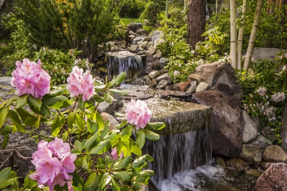 This is a close look at the landscaping of the house with a water feature waterfalls adorned with large decorative rocks and flowering shrubs. Image courtesy of Toptenrealestatedeals.com.
