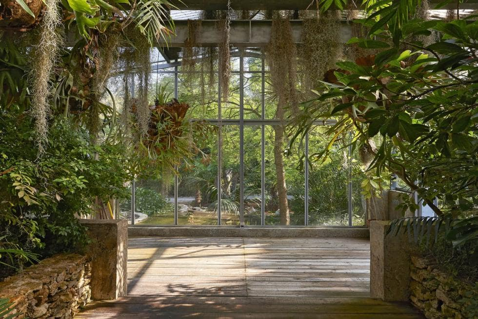 This is a look inside one of the greenhouses of the property with mosaic stone planters, glass walls and hanging plants. Image courtesy of Toptenrealestatedeals.com.