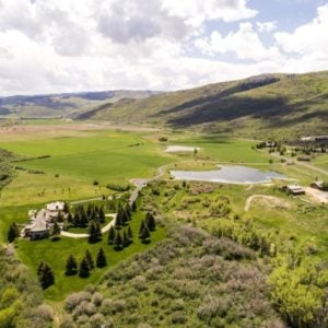 This is an aerial view of the ranch showing the large main house, a pond, spacious fields and the other structures like the barns. Image courtesy of Toptenrealestatedeals.com.
