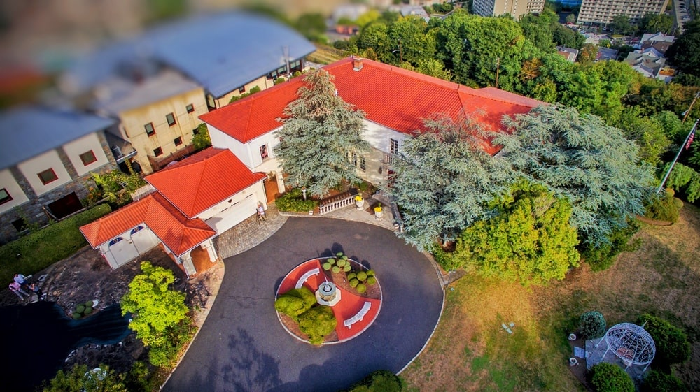 This is an aerial view of the house showcasing the bright red roof of the house that stands out against the surrounding tall trees. Image courtesy of Toptenrealestatedeals.com.