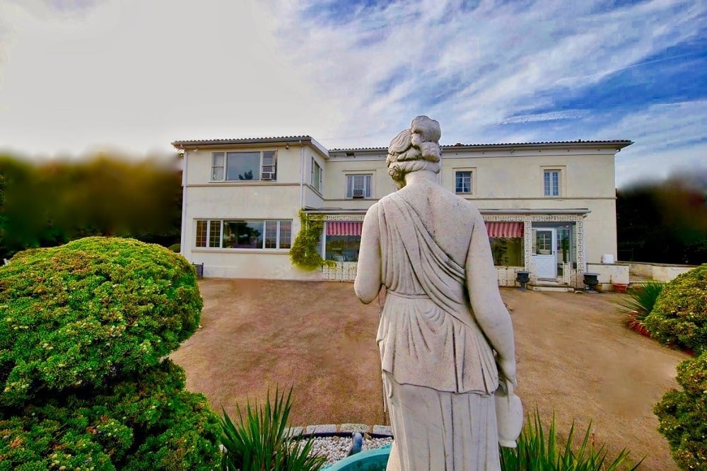 This is a look at the back of the house that has well-manicured shrubs and a large concrete statue of a woman. Image courtesy of Toptenrealestatedeals.com.