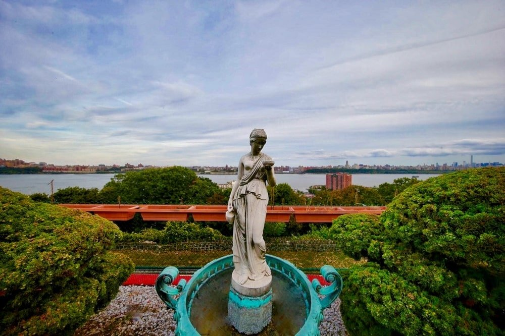 This is a closer look at the view of the river at the back of the house adorned with a large concrete statue. Image courtesy of Toptenrealestatedeals.com.