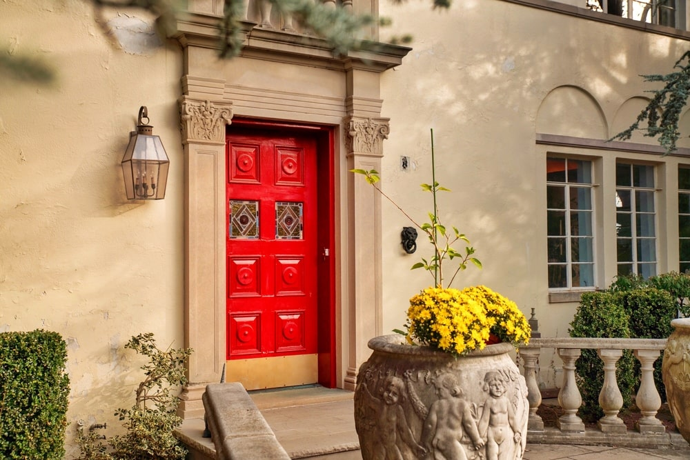 This is a closer look at the main entrance of the house with a vibrant red main door that stands out against the beige walls. Image courtesy of Toptenrealestatedeals.com.