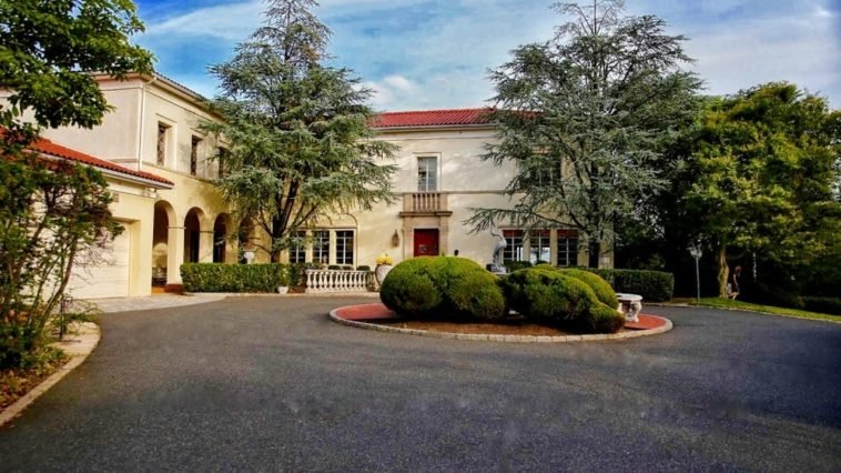 This is a look at the front of the mansion with arches, beige exterior walls and a wide driveway adorned by the small circular garden in the middle across from the main entrance. Image courtesy of Toptenrealestatedeals.com.