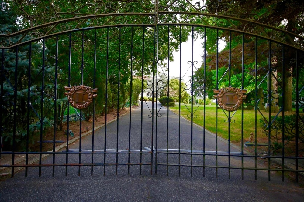 This is a look at the property from the vantage of the main gate. the large wrought-iron gate stands out against the background of lush landscaping. Image courtesy of Toptenrealestatedeals.com.