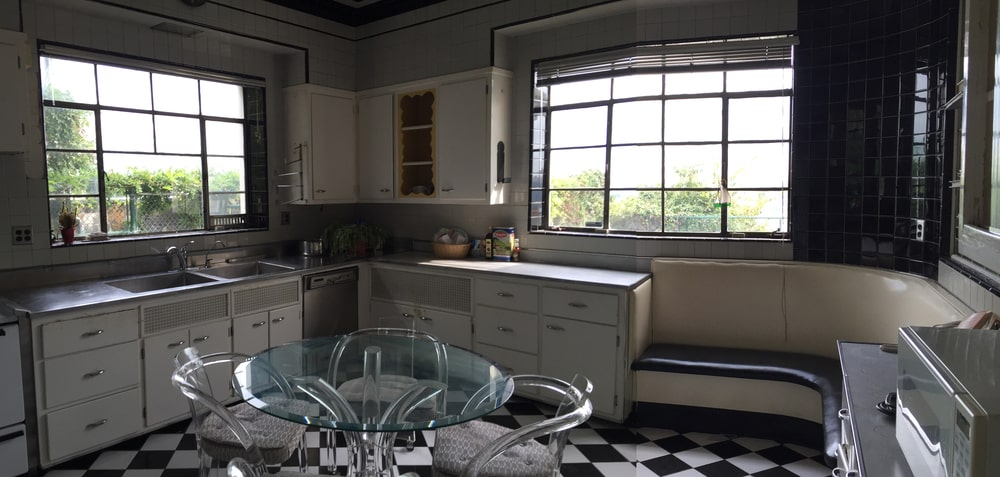 The kitchen has a black and white checkered floor that stands out against the white cabinetry and glass-top round table. Image courtesy of Toptenrealestatedeals.com.