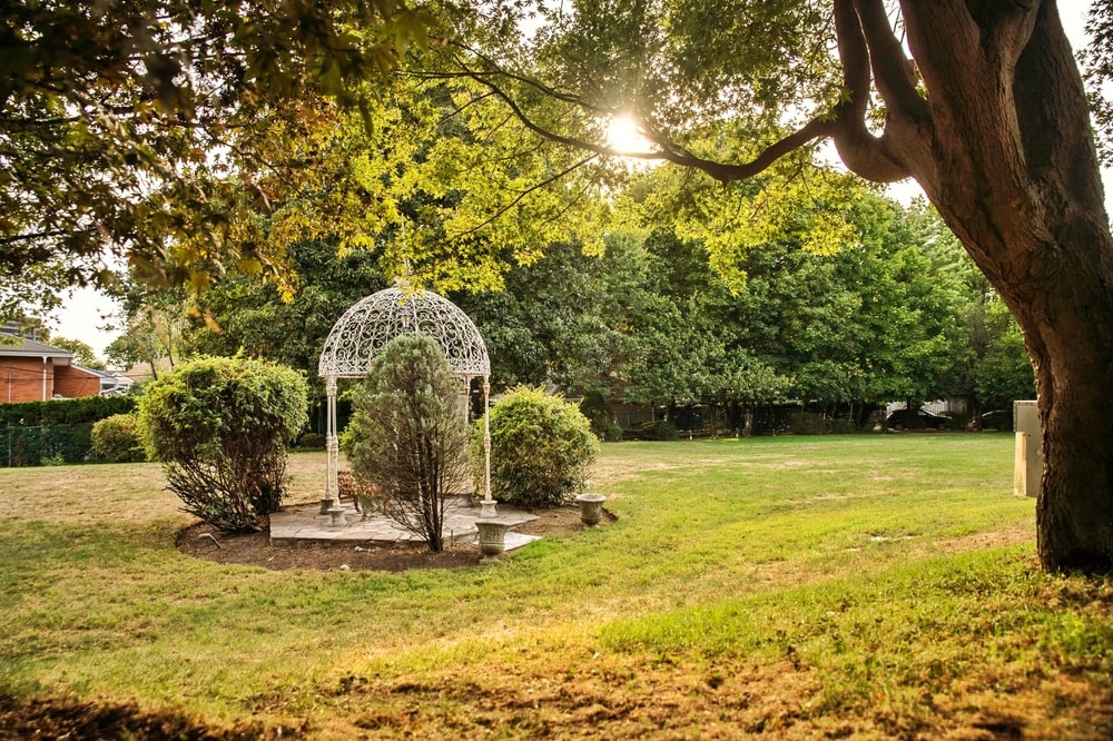 This is a look at the spacious grass lawn of the property with a small gazebo in the middle. Image courtesy of Toptenrealestatedeals.com.