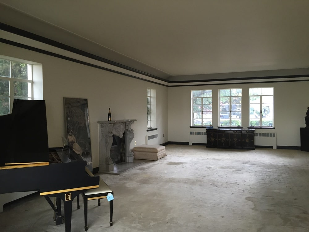 This is a look inside the living room with a large fireplace in the middle of the wall, a grand piano and a set of windows on the far side.Image courtesy of Toptenrealestatedeals.com.