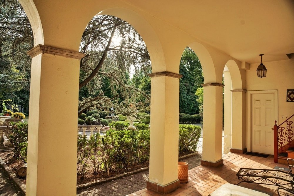 This is the covered patio with rows of arches and pillars that bring in natural lighting to the area bordered with shrubs. Image courtesy of Toptenrealestatedeals.com.