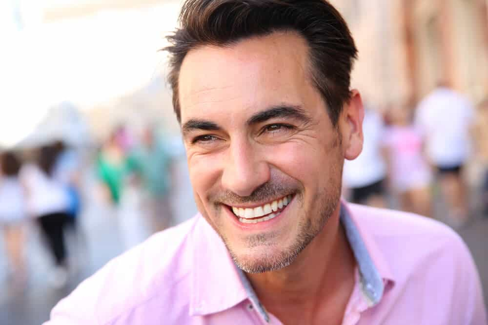 A man smiling. exposing his healthy teeth.