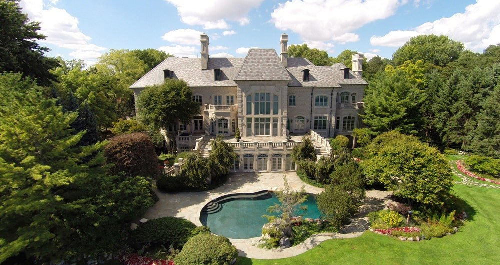 This is an aerial view of the back of the house featuring the backyard pool, the earthy exteriors and the lush green landscape that complements everything. Image courtesy of Toptenrealestatedeals.com.