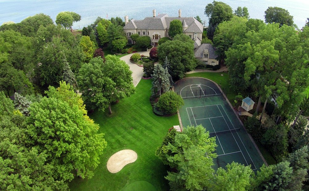 This is an aerial view of the property that showcases the putting green and the tennis court adorned by tall trees. Image courtesy of Toptenrealestatedeals.com.