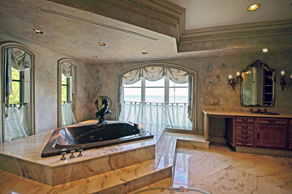 This is the spacious bathroom with a large bathtub embedded with slabs of white marble by the large arched windows. Image courtesy of Toptenrealestatedeals.com.