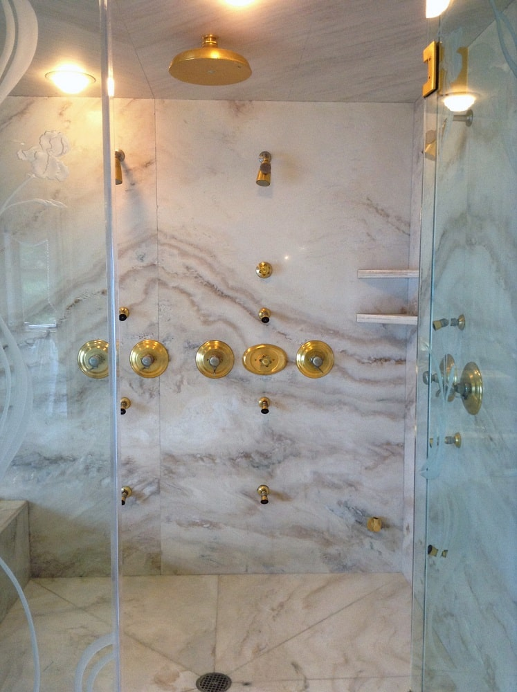 This is a close look at the golden fixtures of the shower area that stands out against the white marble wall. Image courtesy of Toptenrealestatedeals.com.