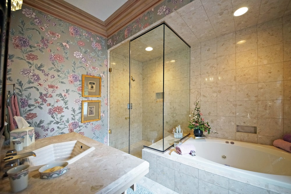 This is a look at the glass-enclosed shower area of this bathroom beside the bathtub that is across from the vanity. Image courtesy of Toptenrealestatedeals.com.
