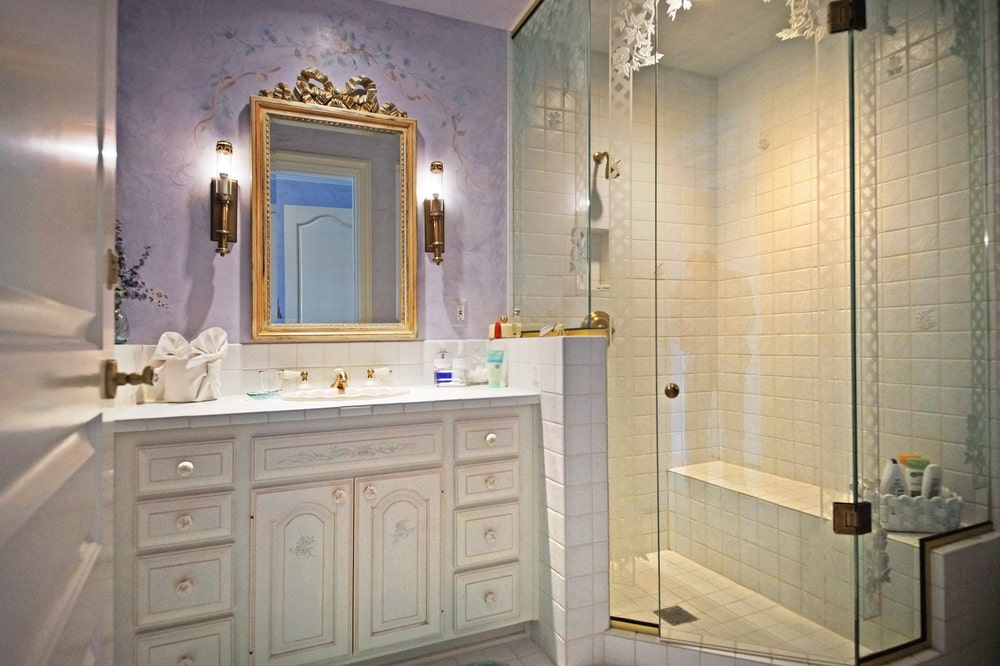 This bathroom has a glass-enclosed shower area beside the beige vanity topped with mirror that has a golden frame. Image courtesy of Toptenrealestatedeals.com.