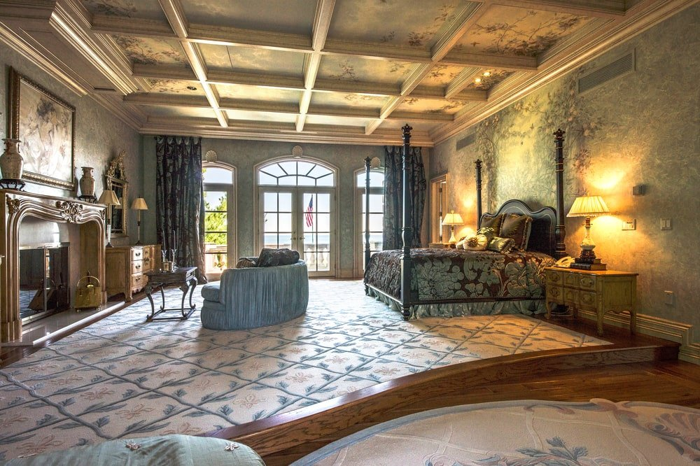 This is the primary bedroom with a large four-poster bed and sitting area across from it by the fireplace. Image courtesy of Toptenrealestatedeals.com.