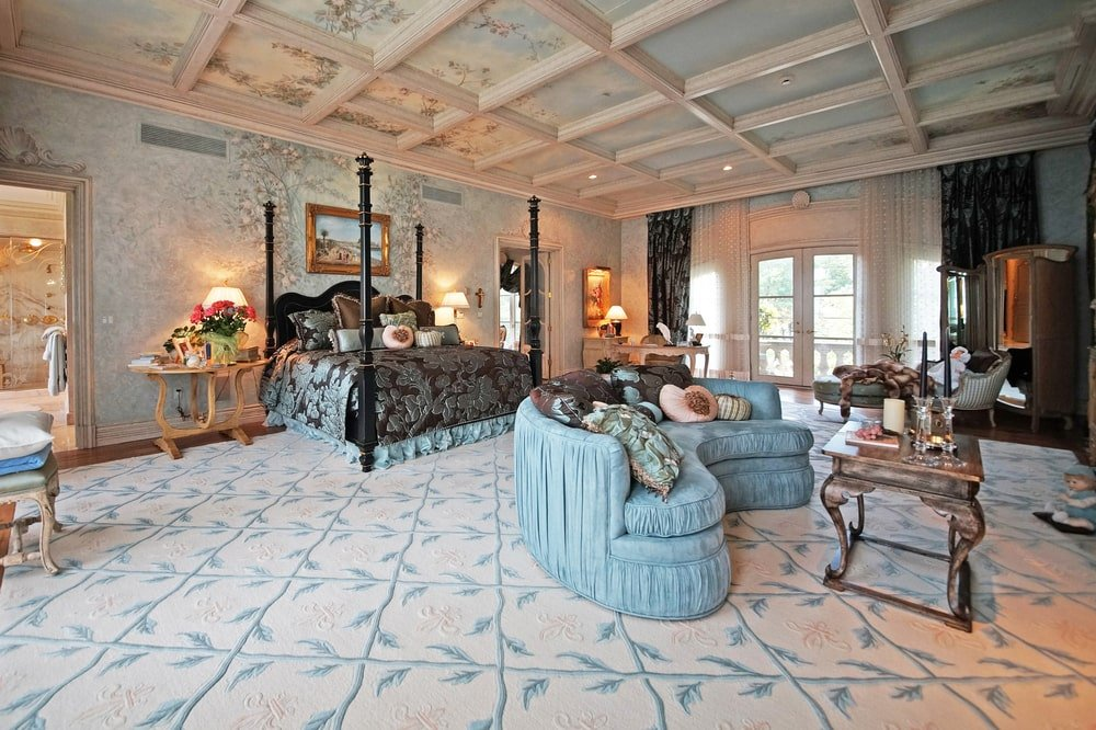 The four-poster bed of this bedroom stands out against the patterned ceiling, walls and carpeted flooring. Image courtesy of Toptenrealestatedeals.com.