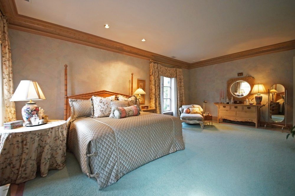 This other bedroom has a large two-poster bed with a wooden headboard that matches the moldings of the ceiling. Image courtesy of Toptenrealestatedeals.com.