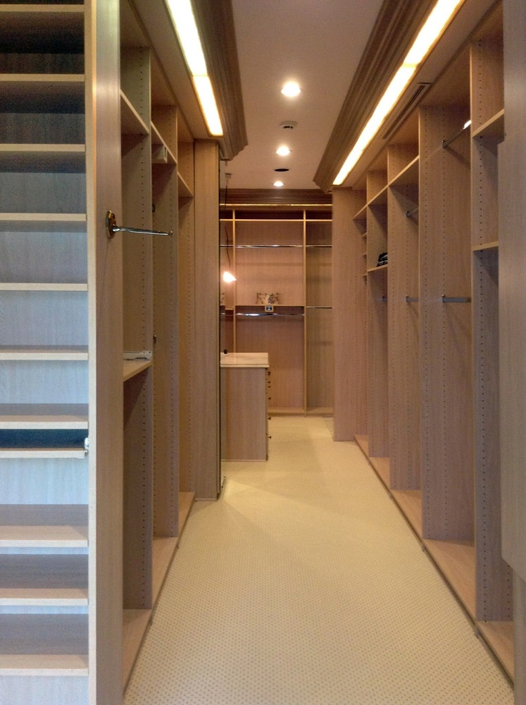 This is the walk-through closet of the primary bedroom with built-in wooden shelves, cabinets and racks. Image courtesy of Toptenrealestatedeals.com.