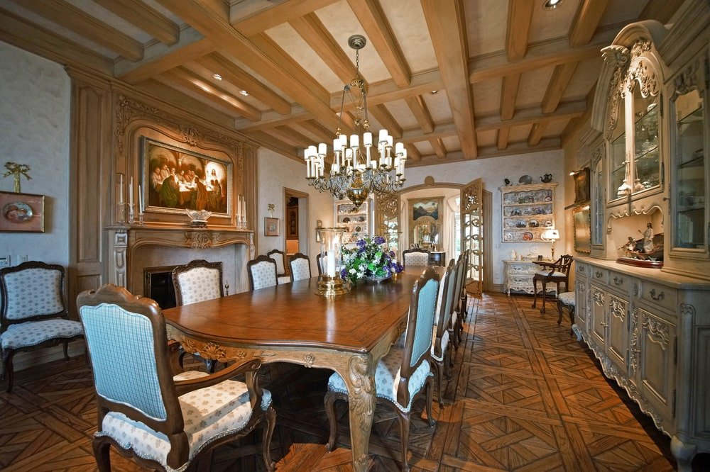 The formal dining room has a large wooden dining table topped with a chandelier. These are complemented by the fireplace on the side topped with a painting. Image courtesy of Toptenrealestatedeals.com.
