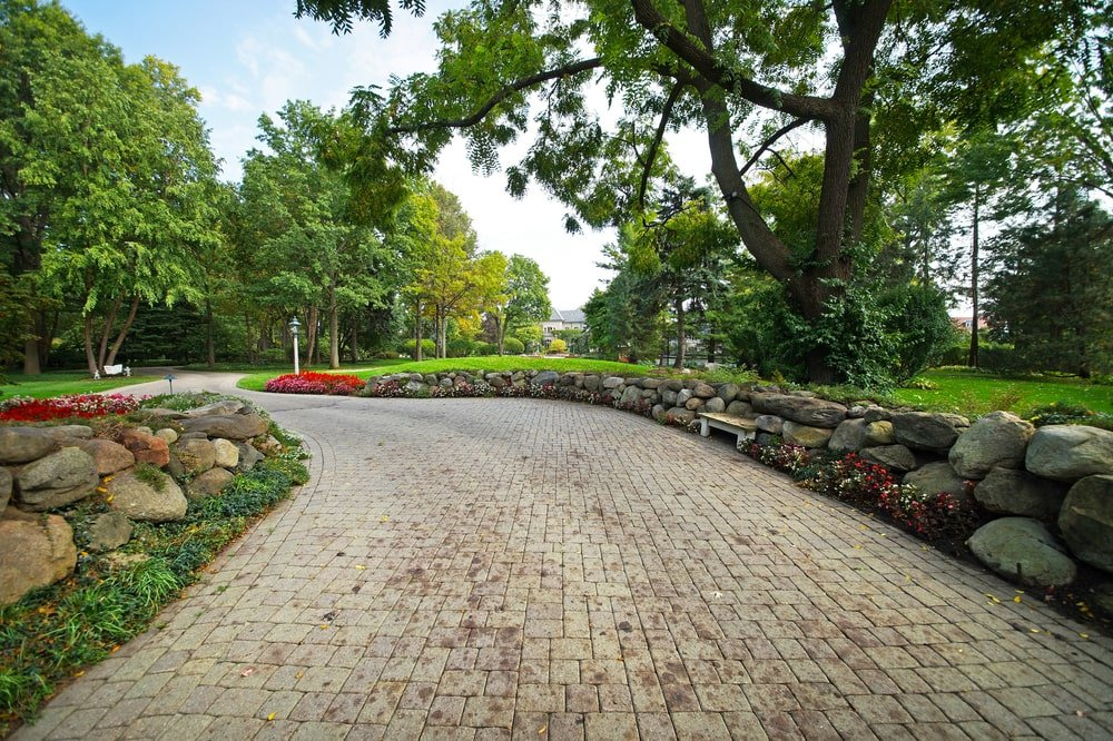 Upon entry of the property from the gate, you go through this wide driveway adorned with decorative stone, flowering shrubs and tall trees. Image courtesy of Toptenrealestatedeals.com.
