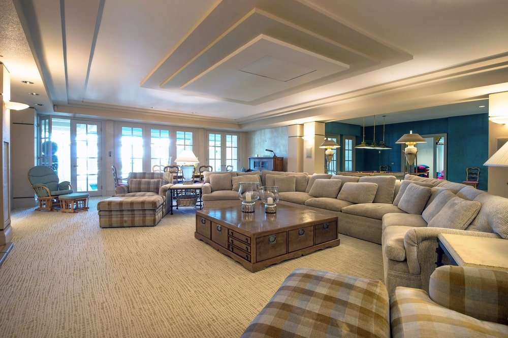 This is the family room with a tray ceiling over the large curved sectional sofa paired with a wooden apothecary coffee table. Image courtesy of Toptenrealestatedeals.com.