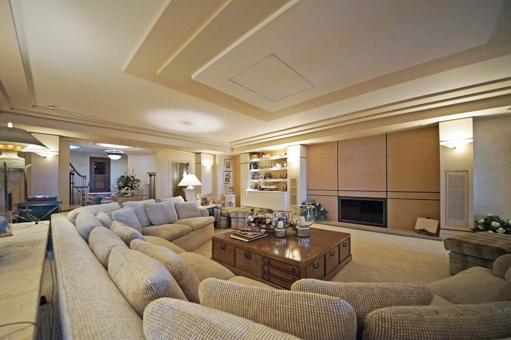 This other look at the family room shows the large curved sectional gray sofa across from the wood-paneled wall housing the fireplace. Image courtesy of Toptenrealestatedeals.com.